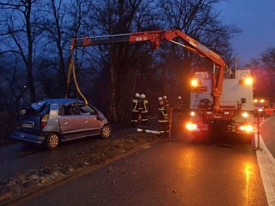 Die Feuerwehr zieht das total beschädigte Auto mit einer Seilwinde aus dem Fluss