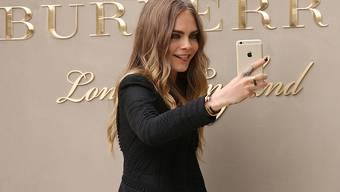 Auf die Luxusmarke Burberry kommen härtere Zeiten zu: Über 140 Millionen Franken sollen eingespart werden. Im Bild posiert das britische Model Cara Delevingne für ein Selfie. (Archivbild)