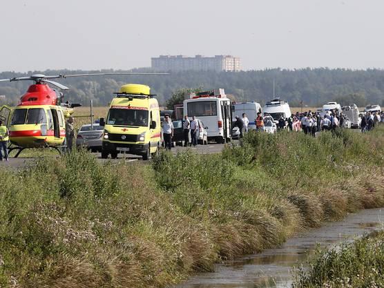 Rettungsfahrzeuge und Helikopter in der Nähe des Maisfeldes, in dem der verunglückte Airbus der Ural Airlines liegt.