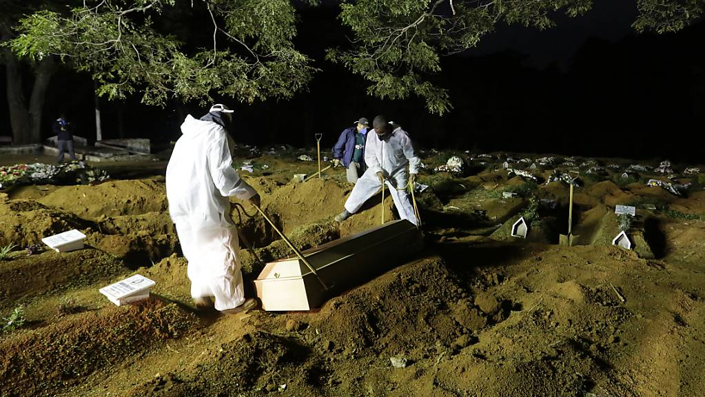 Friedhofsarbeiter in Sao Paulo begraben einen Menschen, der an Komplikationen im Zusammenhang mit Covid-19 gestorben ist. Foto: Nelson Antoine/AP/dpa