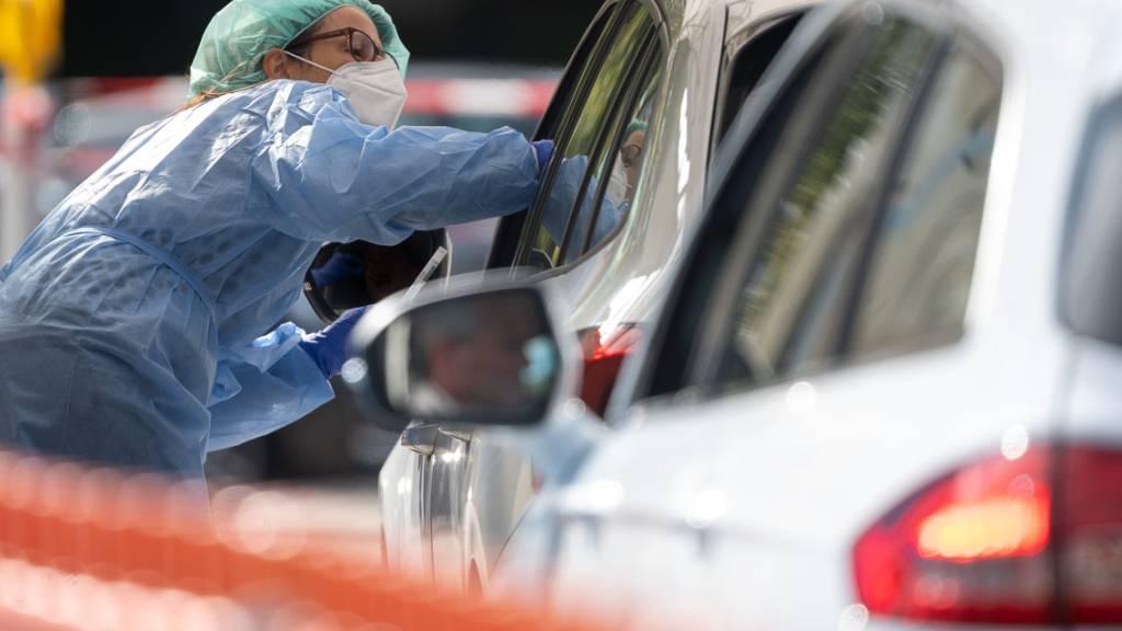 Eine Mitarbeiterin im Landkreis Esslingen macht im Corona-Abstrich-Zentrum bei einem Autofahrer einen Abstrich. Foto: Sebastian Gollnow/dpa