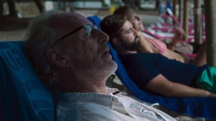 ... liegt ein älterer Mann reglos im Liegestuhl.