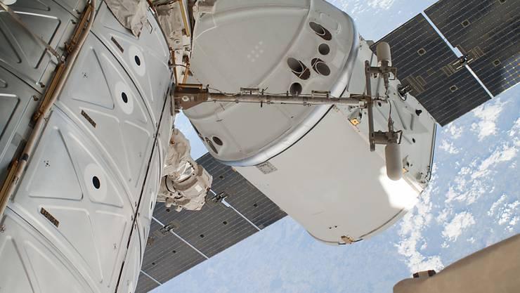 """""""Dragon""""-Raumfrachter an der Internationalen Raumstation ISS. Derzeit herrscht auf der ISS Hochbetrieb: fünf Raumschiffe sind derzeit angedockt. (Themenbild)"""