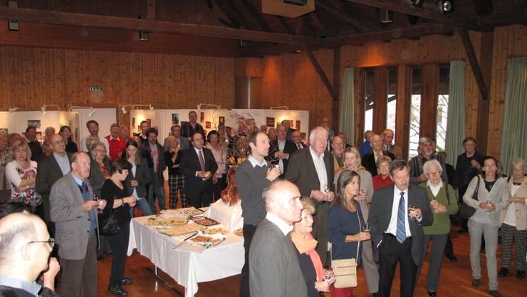 Die Besucher lauschen der Rede von Paul Studer.  Im Hintergrund die Ausstellung «Oetwil lebt!».