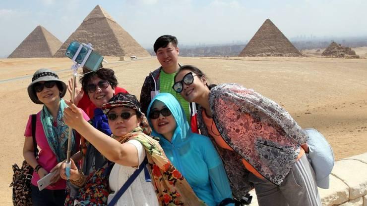 Touristen posieren vor den Pyramiden in Gizeh für ein Selfie. (Archiv)