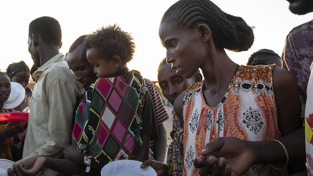 dpatopbilder - Menschen, die vor dem Konflikt in der äthiopischen Region Tigray geflohen sind, warten auf gekochten Reis im Flüchtlingslager Um Rakuba. Foto: Nariman El-Mofty/AP/dpa
