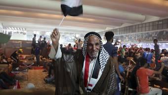 Ein Anhänger von al-Sadr schwenkt die Irak-Flagge im gestürmten Parlamentsgebäude