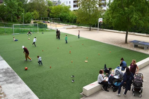 Fussball und Kubb-Spiel auf dem Sportplatz, daneben unterhalten sich die Gäste.