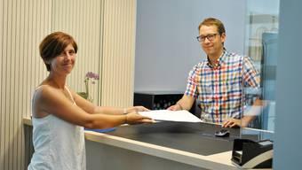 Corinne Zumsteg übergibt Gemeindeschreiber Florian Wunderlin die gesammelten Unterschriften. nbo