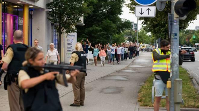 Mit erhobenen Händen kommen Passanten aus dem Olympia-Einkaufszentrum, während Polizisten die Strassen sichern. Foto: Getty Images/Jörg Koch