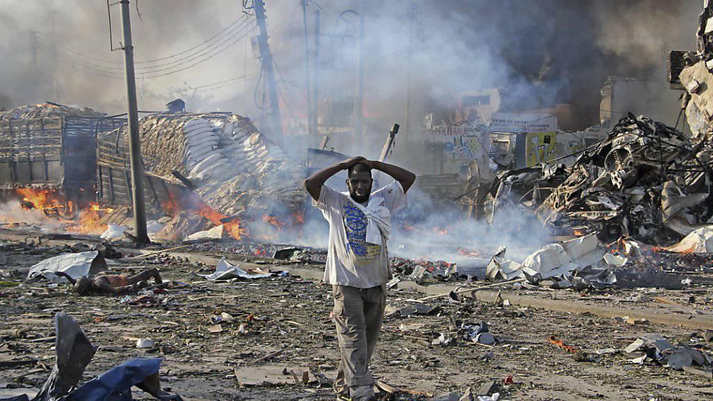 Ein Bewohner Mogadischus läuft traumatisiert an Leichen und Trümmern vorbei: Die Lastwagenexplosion war gewaltig und beschädigte auch die umliegenden Gebäude schwer.