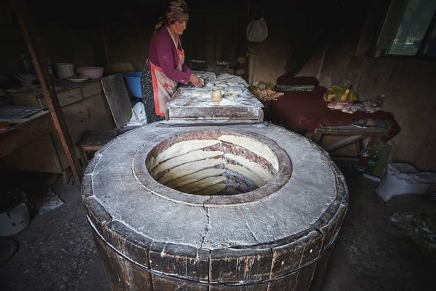Das traditionelle Fladenbrot Tonis Puri wird zum Backen an die Innenseite des Ofens geklatscht.