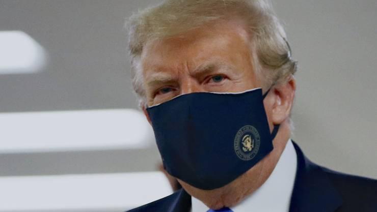US-Präsident Donald Trump mit einem Stoff-Mundschutz, auf dem das Präsidenten-Siegel abgebildet ist.