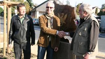 Felix Naef, Gemeindeammann Martin Steinacher und Holzbildhauer Traugott Erdin (von links) an der Skulptur auf dem neuen Dorfplatz.