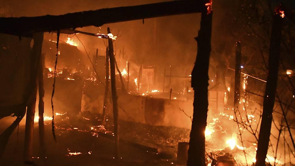 Feuer brennt außerhalb des überfüllten Flüchtlingslagers am Hafen von Vathy auf der ostägäischen Insel Samos, Griechenland. Am späten Sonntagabend ist aus bisher unbekannten Ursachen im alten Flüchtlingslager auf der griechischen Insel Samos in Brand ausgebrochen. Foto: Michael Svarnias/AP/dpa