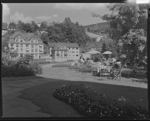 """Kurgäste im Park des Badener Verenahofs. Auf der anderen Seite der Limmat das """"National"""" und der alte """"Hirschen"""" (rechts)."""
