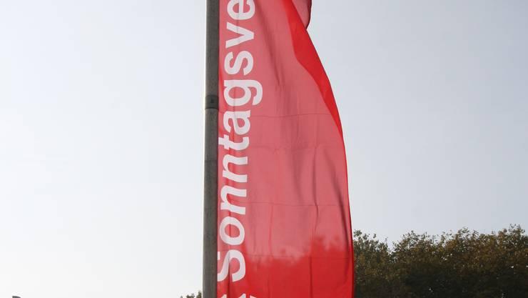 Neu wirbt eine Brücken-Beflaggung für den Sonntagsverkauf.