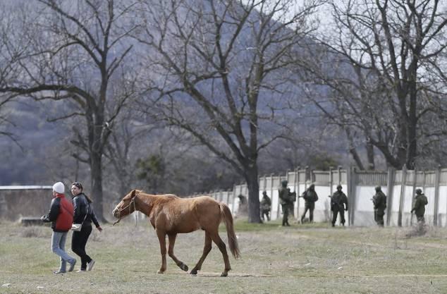 Frauen führen ein Pferd aus der übernommenen ukrainischen Militärzone nahe Simferopol.