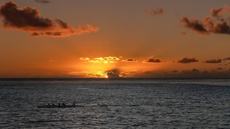 Einheimische rudern während des Sonnenuntergangs