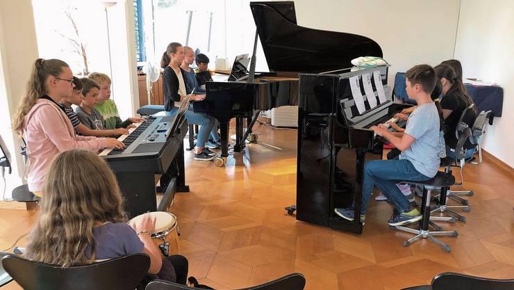 Schülerinnen und Schüller von Lehrerin Anna Wittmer beim Klavierensemblespiel an einem Tag des Projekts Offener Musikschule.