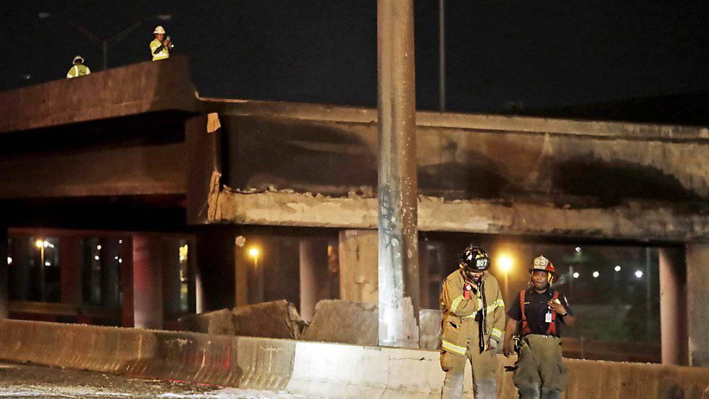 Feuerwehrmänner überwachen die zerstörte Autobahnbrücke in Atlanta - ein Feuer brachte die Brücke zum Einstzurz.