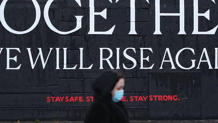 Eine Frau geht an einem Wandbild im Stadtzentrum von Dublin vorbei, das den Bürgern in der Corona-Zeit Mut machen soll. Foto: Niall Carson/PA Wire/dpa