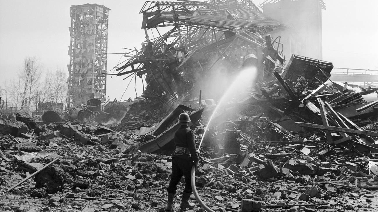 Ein Feuerwehrmann beim Löschen in den Trümmern nach der Explosion in der Schweizerischen Sprengstoff-Fabrik (© Keystone)