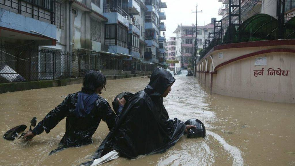 Nepalesen waten mit ihrem Motorrad durch die überfluteten Strassen der Hauptstadt Kathmandu.