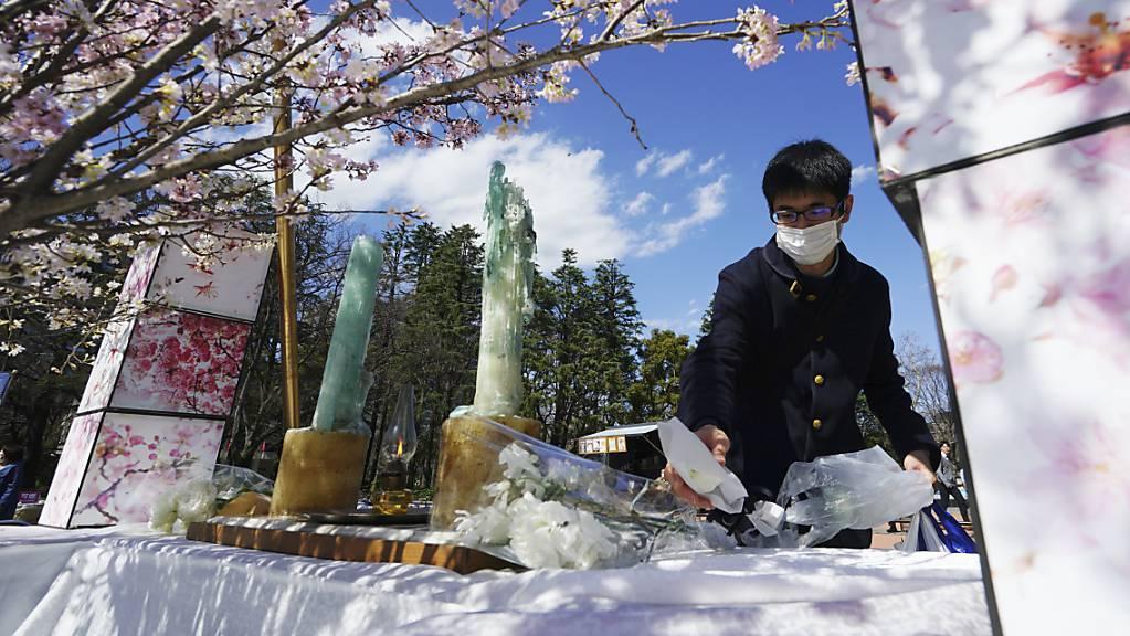 Ein Mann legt in Tokio Blumen für die Opfer der Atomkatastrophe von Fukushima vor neun Jahren nieder - wegen der Corona-Epidemie wurde die öffentliche Gedenkzeremonie abgesagt.