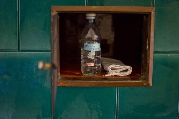 Die Weihwassernachfüllflasche im Kachelofen