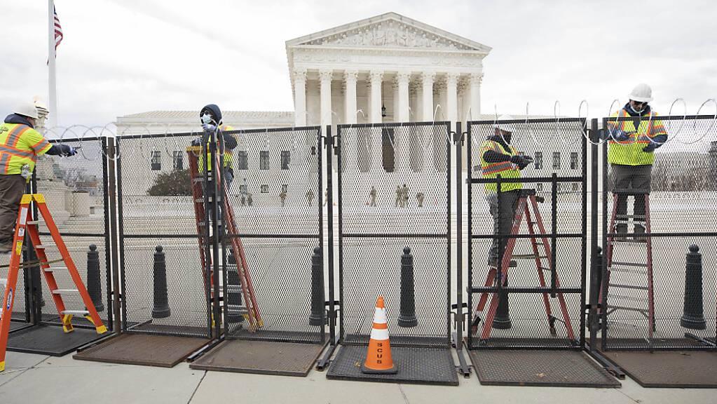 ARCHIV - Arbeiter stehen am Zaun vor dem US-Kapitol während der Sicherheitsvorbereitungen vor der Wiedereröffnung des Gebäudes. Gut acht Monate nach der Erstürmung des Kapitols in Washington bereitet sich die Polizei auf eine weitere Demonstration durch Anhänger des damaligen US-Präsidenten Donald Trump vor. Foto: Mark Finkenstaedt/ZUMA Wire/dpa