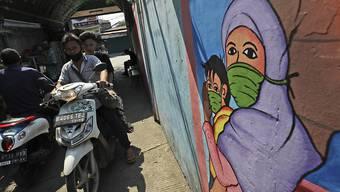 Ein Wandbild in Jakarta zeigt eine Frau und ein Kind, die Mundschutz tragen. Foto: Dita Alangkara/AP/dpa