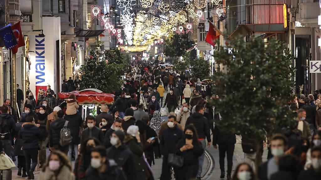 Menschen spazieren wenige Stunden vor der Sperrstunde entlang der Haupteinkaufsstraße in Istanbul. Die türkische Regierung hat entgegen der bisherigen Praxis die täglichen Fallzahlen der positiv auf das Coronavirus getesteten Menschen im Land bekanntgegeben. Foto: Emrah Gurel/AP/dpa