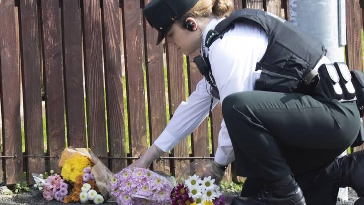Eine Polizistin legt Blumen nieder, wo die Journalistin Lyra McKee von einer Kugel getroffen wurde und starb. Die Ordnungshüter vermuten, dass katholische Extremisten hinter der Tat stehen.