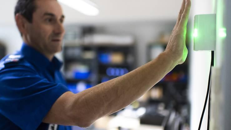 Ein Polizist demonstriert einen zu Testzwecken montierten Handvenen-Scanner. Die Stadtpolizei St. Gallen führt das biometrische Identifikationssystem ein, um die Sicherheit zu verbessern.