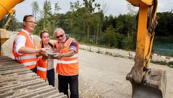 Sie besprechen das Vorgehen zum Schütten der Kiesbank: Ulrich Harder (links, Amt für Umwelt, Wasserbau), Sara Bieler (BSB, Bauingenieurin in Ausbildung) und Hans Studer (Oberbauleiter).