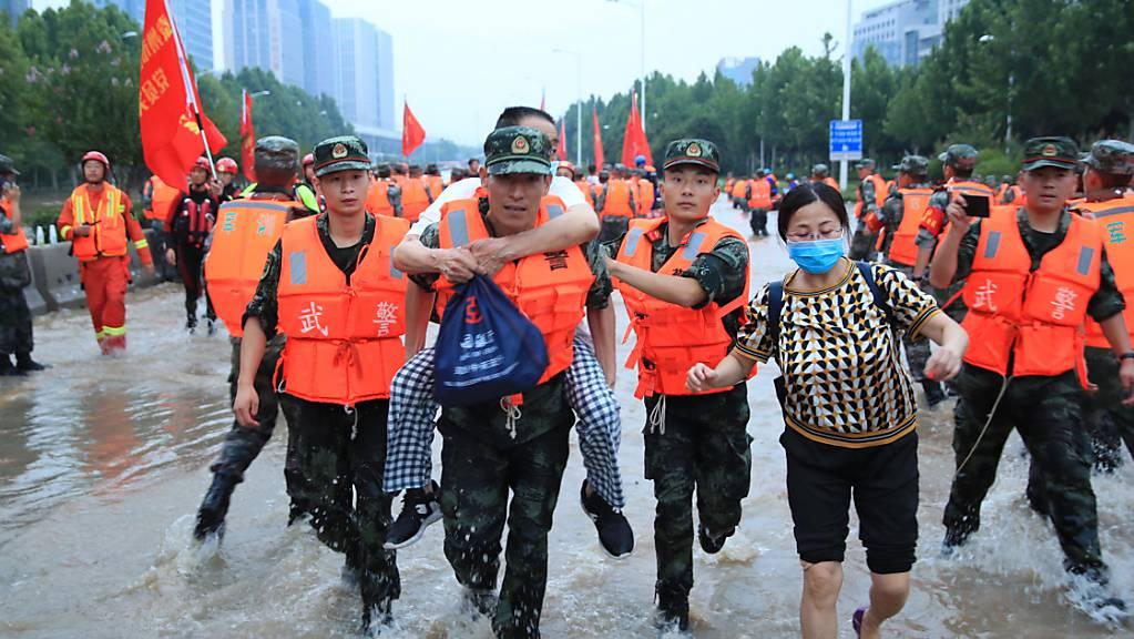 Mitarbeiter des Militärs tragen Patienten eines Krankenhauses über eine überschwemmte Straße. Laut Angaben des chinesische Staatsfernsehens am Freitag ist die Zahl der Toten nach den schweren Überschwemmungen in der chinesischen Metropole Zhengzhou auf 56 gestiegen. Foto: Uncredited/CHINATOPIX/AP/dpa