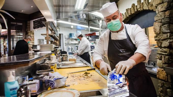Köche bereiten Essen in einem Restaurant in Losone zu.