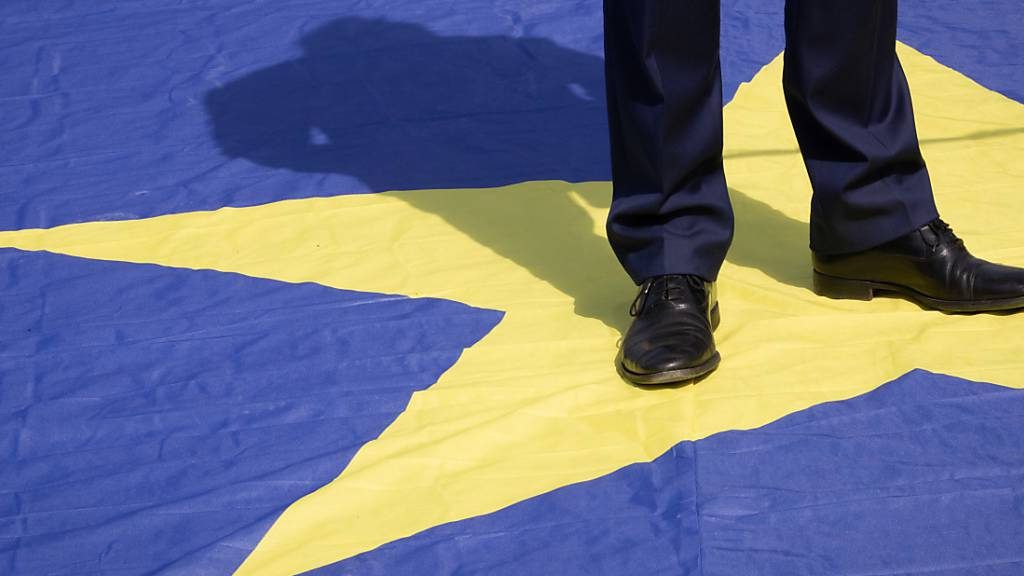 Die Beine eines Mannes auf einem Stern einer europäischen Flagge. Foto: Benoit Doppagne/BELGA/dpa