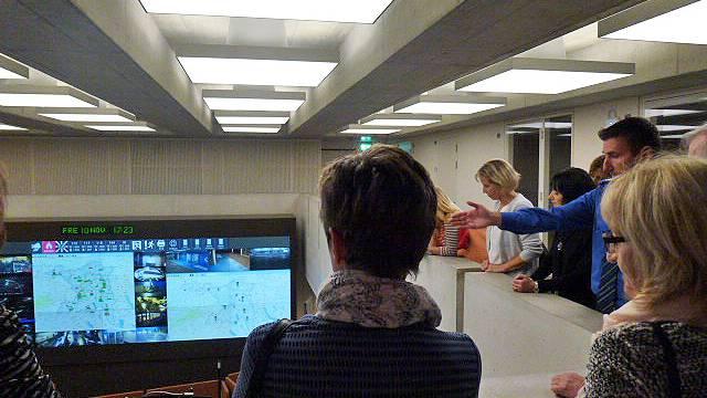 Die Mitarbeitenden des Rotkreuz-Notrufs beobachten, wie die in der kantonalen Notrufzentrale die Anrufe bearbeitet werden.