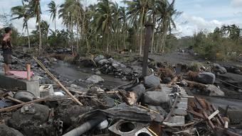 """Ein Mann betrachtet die Schäden, die Taifun """"Goni"""" am Vulkan Mayon angerichtet hat. Foto: John Michael Magdasoc/AP/dpa"""