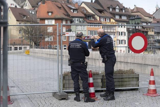Zwei Grenzwächter bringen an der Absperrung Informationen an.