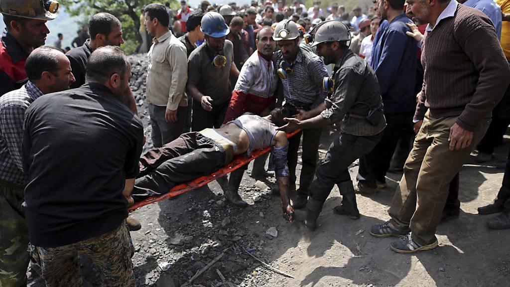 Kumpel und Rettungskräfte tragen einen Verletzten zur Ambulanz. Die Bergungsarbeiten gestalten sich schwierig, einige Kumpel sind noch im Bergwerk eingeschlossen.