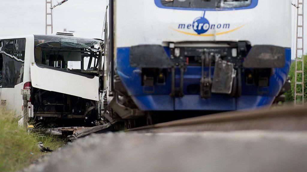 Ein Zug kollidiert mit einem Gelenkbus, der mit einer Panne auf dem Bahnübergang liegengeblieben war. Dank der Geistesgegenwart der Buschauffeurin konnten alle 60 Kinder den Bus noch vor der Kollision verlassen.