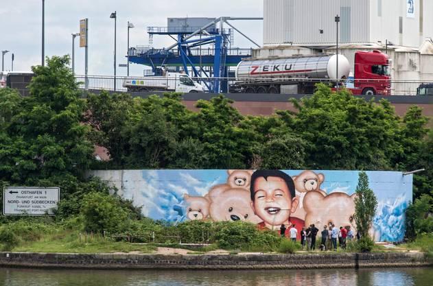 Auf die Verunstaltung des Bilds in Frankfurt folgte ein neues. Es zeigt den lachenden Aylan umringt von Teddybären.
