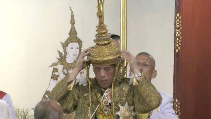 Der feierliche Moment: Thailands König Maha Vajiralongkorn setzt sich auf dem Thron sitzend die Krone auf.