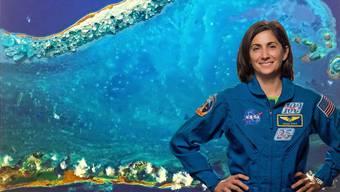Nicole Stott vor dem (stark vergrösserten) Bild der «Welle», das sie auf der ISS gemalt hat.