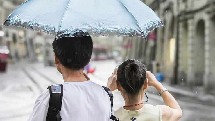 Es braucht wieder einen Regenschirm: Touristen fotografieren die Altstadt von Bern. (Archiv)