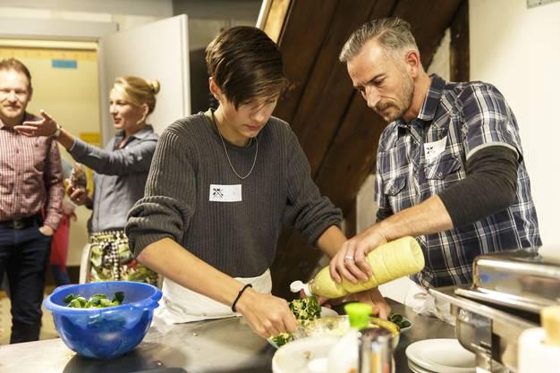 Vorne richtet Reto Hirter mit Joel das Essen her, hinten begrüsst Simone Hirter die neuen Gäste