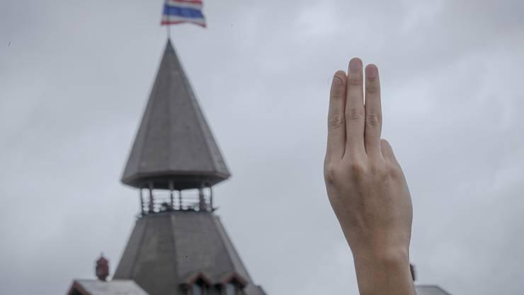 ARCHIV - Ein pro-demokratischer Demonstrant erhebt während einer Demonstration im Sanam-Luang-Park drei Finger als Symbol des Widerstands. Foto: Wason Wanichakorn/AP/dpa